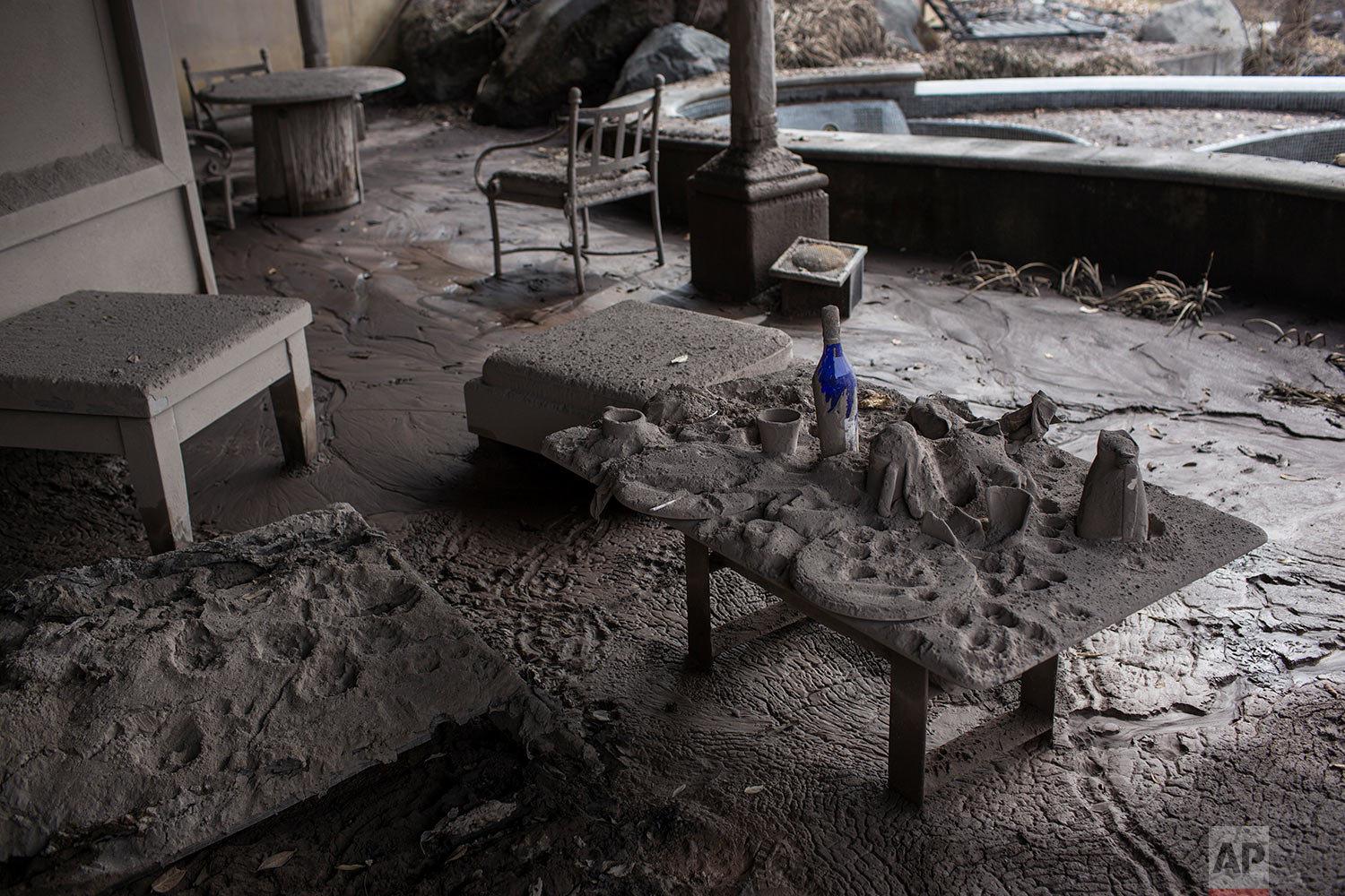 A table with plates and bottles sits blanketed in volcanic ash at the golf resort.San Miguel Los Lotes. June 16, 2018. (AP Photo/Rodrigo Abd)