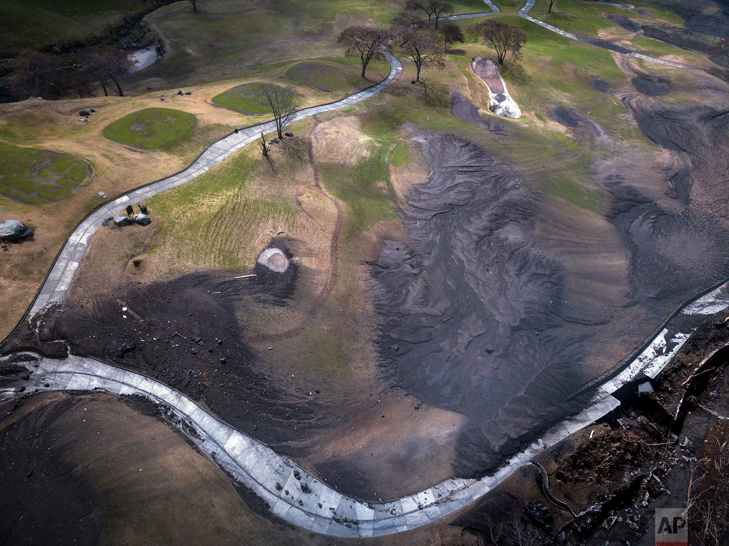 In this June 19, 2018 photo, volcanic debris covers La Reunion Golf Resort & Residences after the eruption of the Volcano of Fire in San Miguel Los Lotes, Guatemala. (AP Photo/Rodrigo Abd)