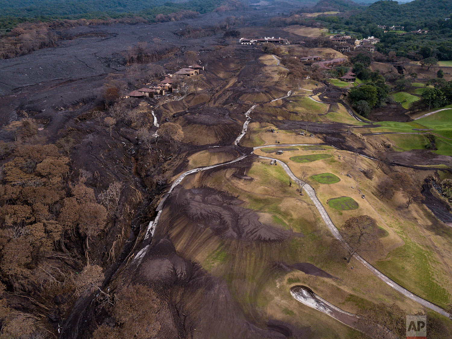 In this June 16, 2018 photo, volcanic debris covers parts of La Reunion Golf Resort & Residences after the eruption of the Volcano of Fire in San Miguel Los Lotes, Guatemala. (AP Photo/Rodrigo Abd)