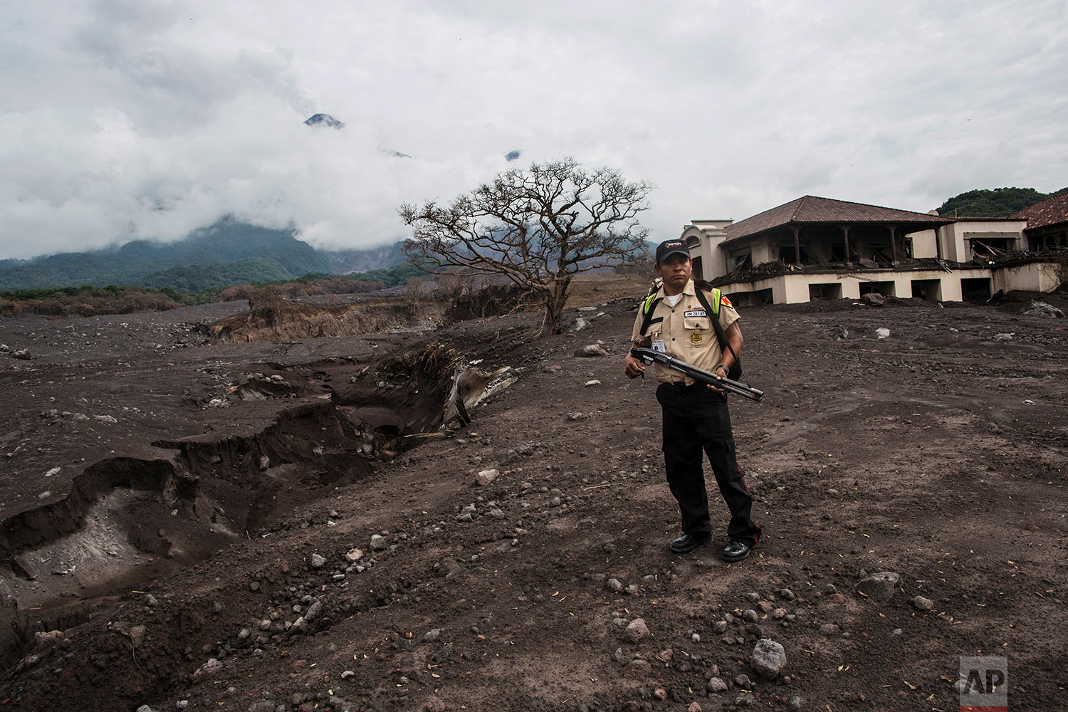 In this June 16, 2018 photo, a private security worker stands guard at La Reunion Golf Resort & Residences after the eruption of the Volcano of Fire in San Miguel Los Lotes, Guatemala. (AP Photo/Rodrigo Abd)
