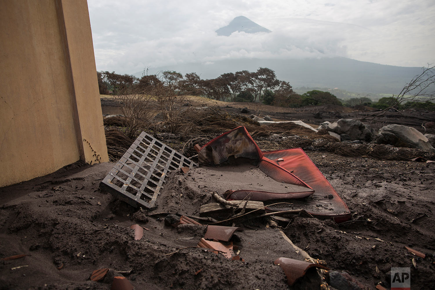 In this June 16, 2018 photo, a lounge chair lays amid volcanic debris in the yard of a home at La Reunion Golf Resort & Residences, destroyed by the eruption of the Volcano of Fire in San Miguel Los Lotes, Guatemala. (AP Photo/Rodrigo Abd)