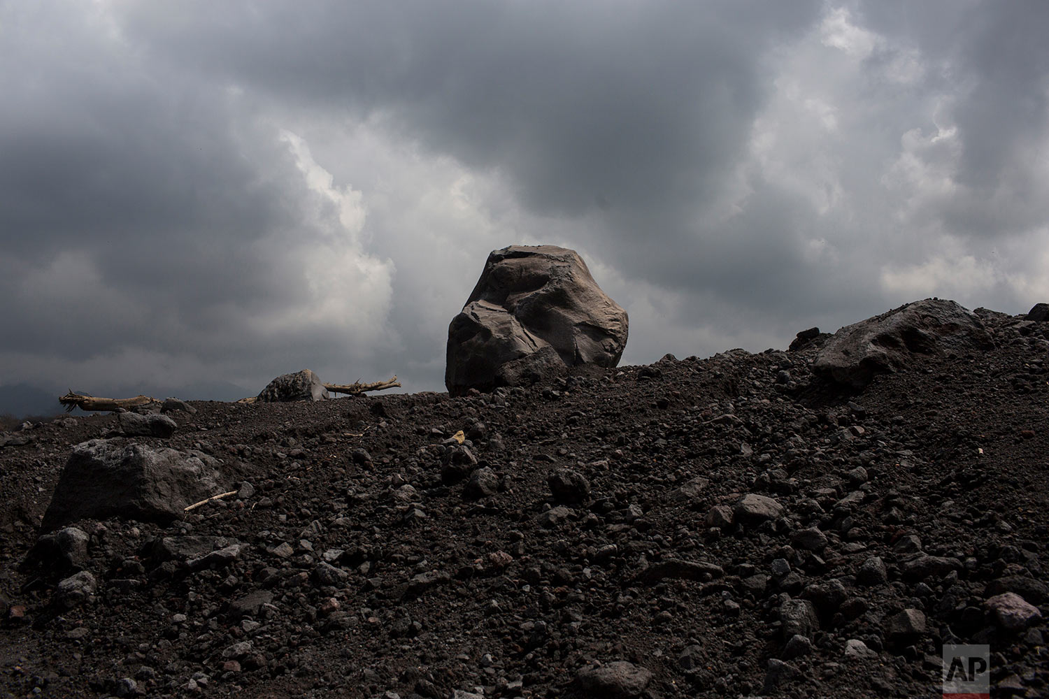 In this June 19, 2018 photo, a boulder stands on the slopes of the Volcano of Fire along its path of destruction in the aftermath of its eruption in San Miguel Los Lotes, Guatemala. (AP Photo/Rodrigo Abd)