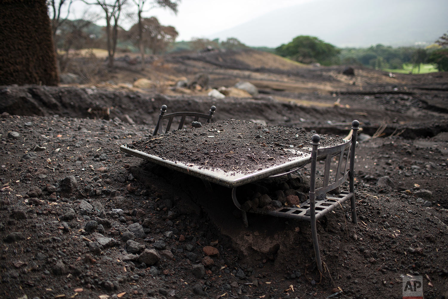 In this June 16, 2018 photo, a table sits buried in volcanic ash on the patio of La Reunion Golf Resort & Residences destroyed by the eruption of the Volcano of Fire in San Miguel Los Lotes, Guatemala. (AP Photo/Rodrigo Abd)