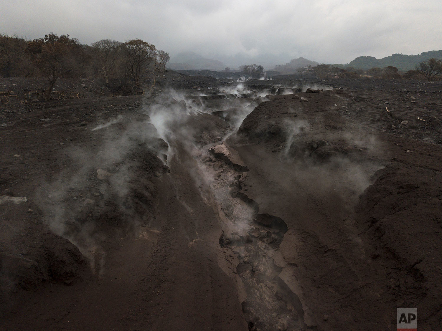 In this June 15, 2018 photo, steam rises from the charred earth after a heavy rain along the path of destruction in the aftermath of the Volcano of Fire's eruption in San Miguel Los Lotes, Guatemala. (AP Photo/Rodrigo Abd)