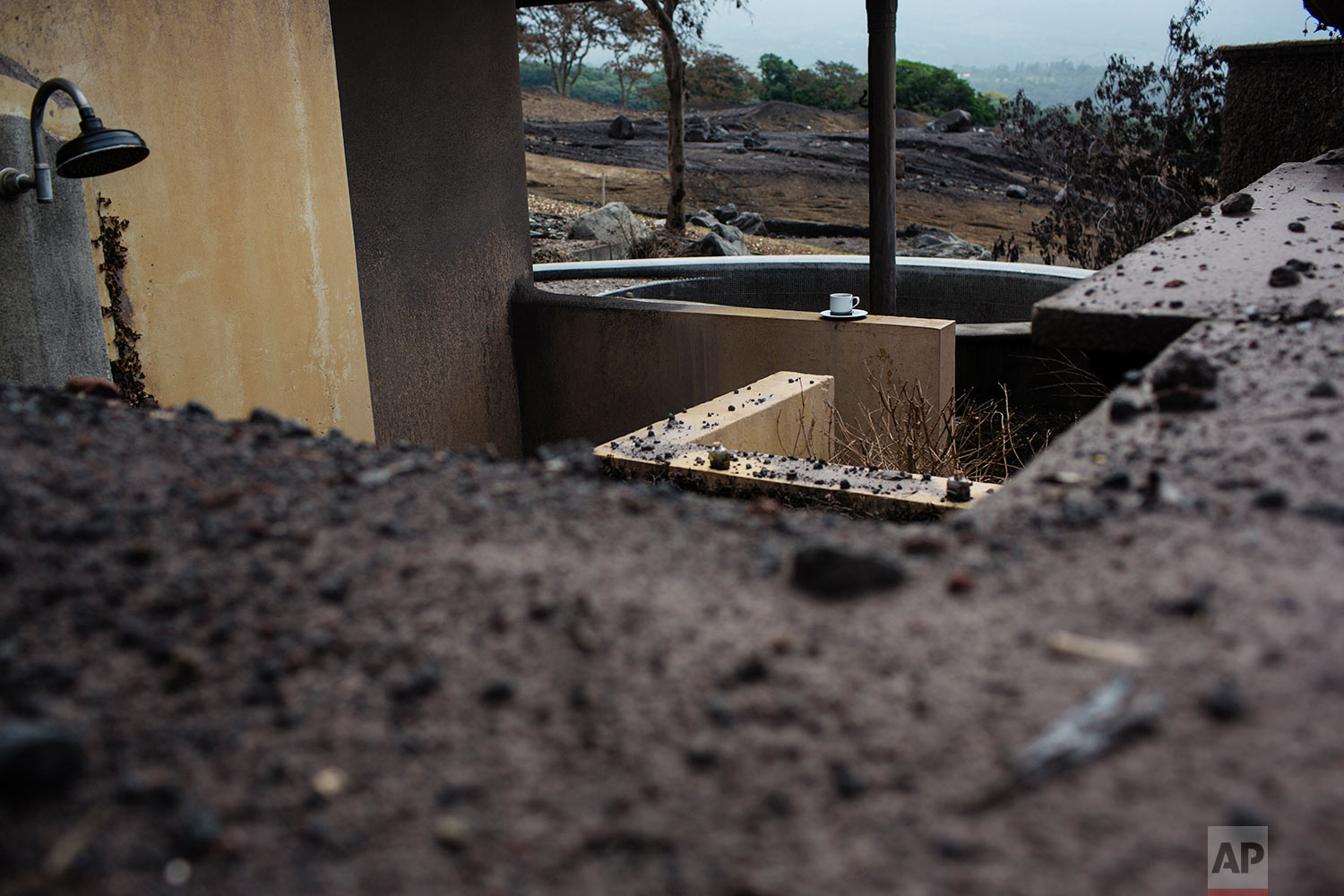 In this June 16, 2018 photo, a coffee cup remains on the rim of a pool at La Reunion Golf Resort & Residences, destroyed by the eruption of the Volcano of Fire in San Miguel Los Lotes, Guatemala. (AP Photo/Rodrigo Abd)