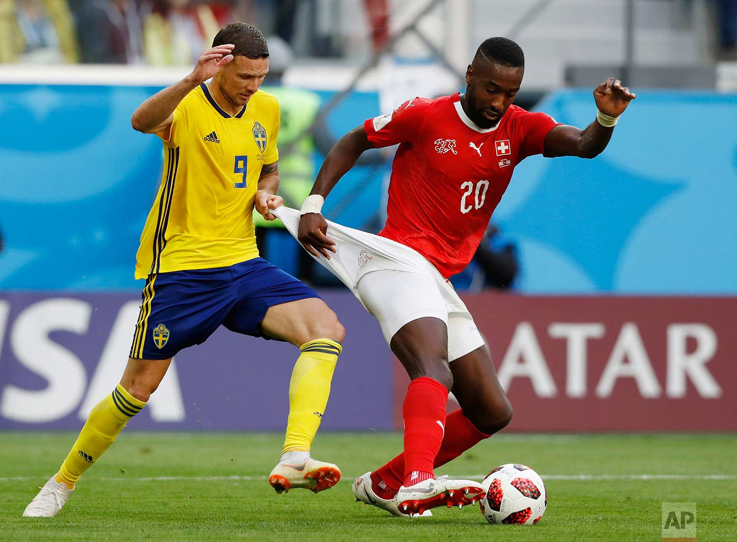 Sweden's Marcus Berg, left, battles for the ball with Switzerland's Johan Djourou during the round of 16 match between Switzerland and Sweden at the 2018 soccer World Cup in the St. Petersburg Stadium, in St. Petersburg, Russia, Tuesday, July 3, 2018. (AP Photo/Darko Bandic)