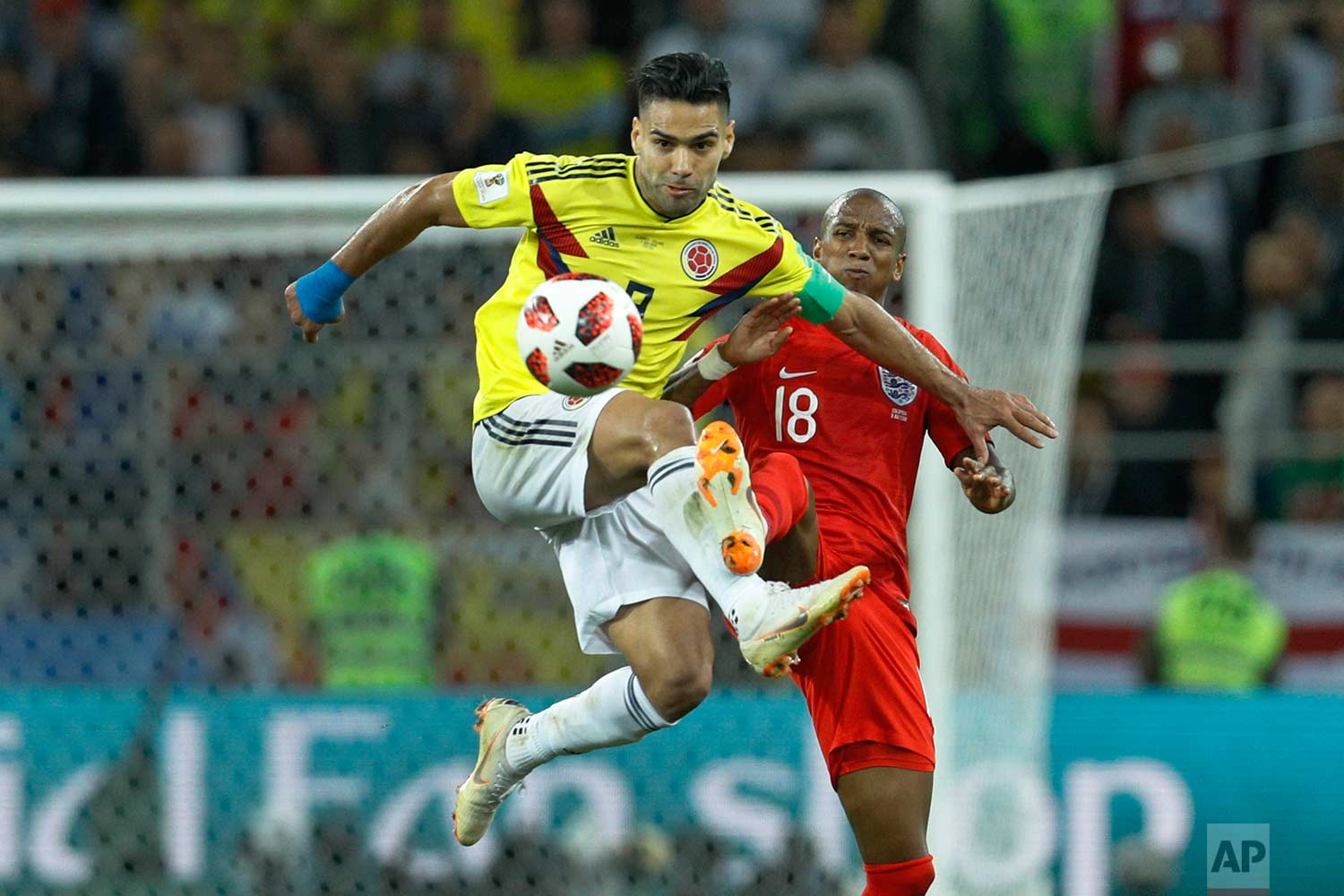 Colombia's Radamel Falcao, left, vies for a ball with England's Ashley Young during the round of 16 match between Colombia and England at the 2018 soccer World Cup in the Spartak Stadium, in Moscow, Russia, Tuesday, July 3, 2018. (AP Photo/Victor R. Caivano)