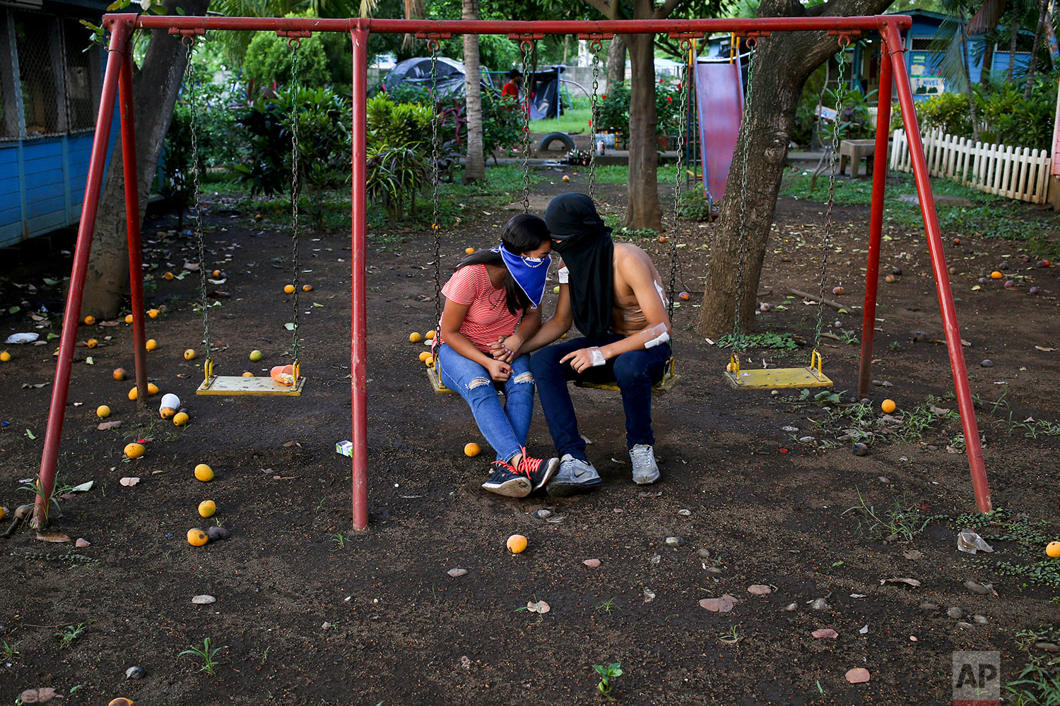 In this June 1, 2018 photo, university students share a moment on a swing set inside the Autonomous University of Nicaragua where anti-government students have barricaded themselves on campus for protection from government security forces and armed supporters in Managua, Nicaragua. (AP Photo/Esteban Felix)