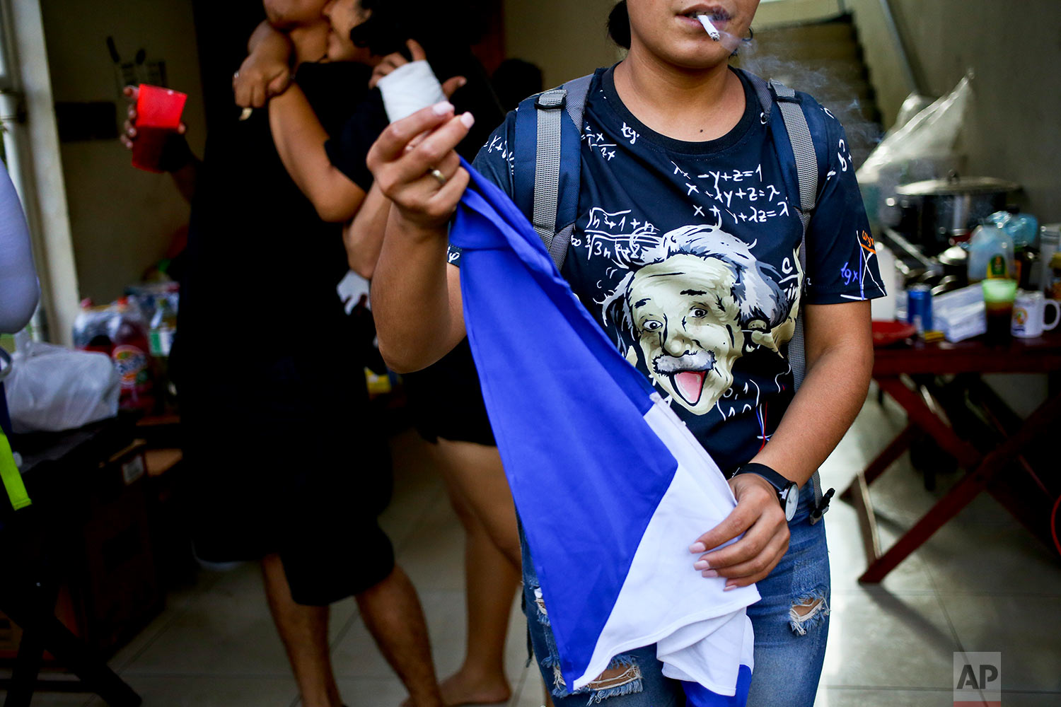 In this June 1, 2018 photo, a university student wears an Albert Einstein T-shirt as she smokes inside an improvised kitchen set up by anti-government students who are barricading themselves inside the Autonomous University of Nicaragua for protection from government security and armed supporters in Managua, Nicaragua. (AP Photo/Esteban Felix)
