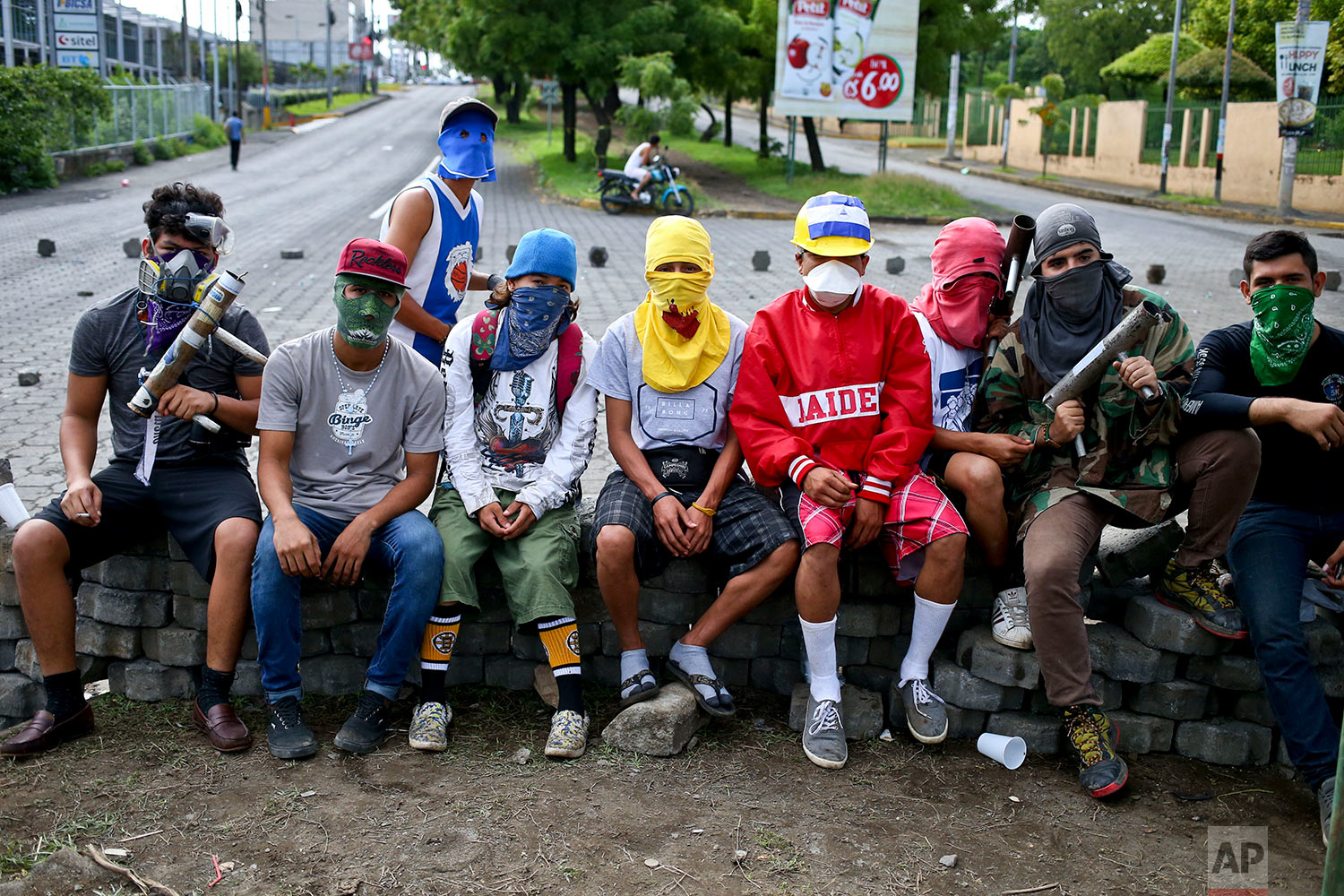 In this June 8, 2018 photo, university students and anti-government protesters poses for a portrait in their masks at a barricade they set up behind an entrance to the Autonomous University of Nicaragua, where students are barricading themselves inside for protection from government security forces and armed supporters in Managua, Nicaragua. (AP Photo/Esteban Felix)