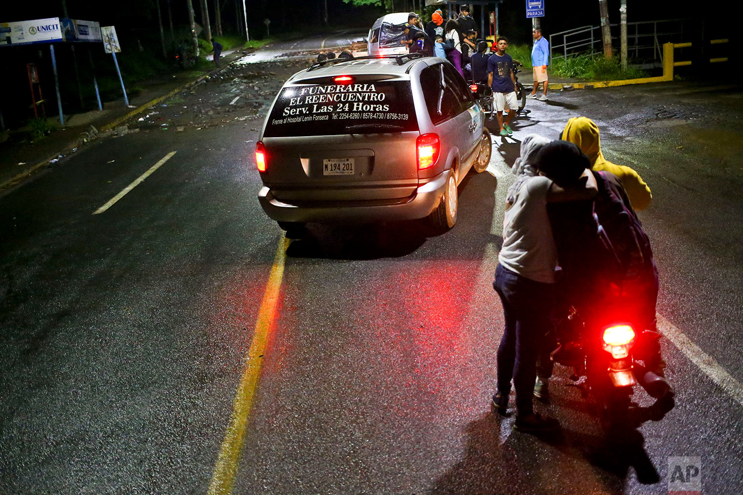 In this June 8, 2018 photo, a funeral home car takes the body of slain high school student Chester Chavarria to the Autonomous University of Nicaragua where anti-government students have barricaded themselves inside in Managua, Nicaragua, on the way to the Chavarria family home for a wake. (AP Photo/Esteban Felix)