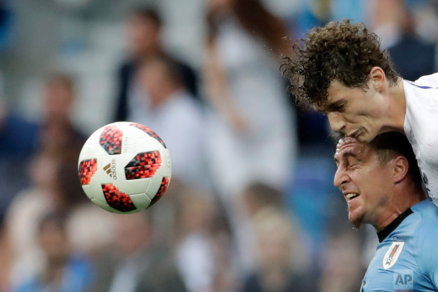 France's Benjamin Pavard, top, and Uruguay's Cristian Rodriguez challenge for the ball during the quarterfinal match between Uruguay and France at the 2018 soccer World Cup in the Nizhny Novgorod Stadium, in Nizhny Novgorod, Russia, Friday, July 6, 2018. (AP Photo/Petr David Josek)