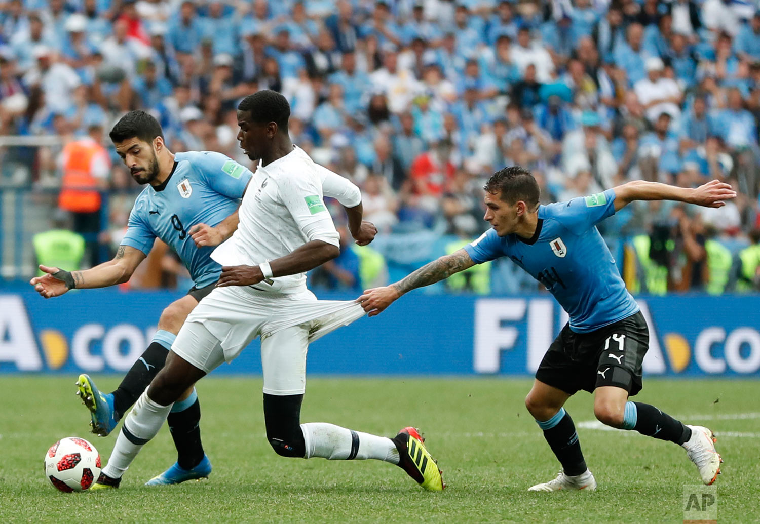 France's Paul Pogba, center, clashes with Uruguay's Luis Suarez, left, and Lucas Torreira during the quarterfinal match between Uruguay and France at the 2018 soccer World Cup in the Nizhny Novgorod Stadium, in Nizhny Novgorod, Russia, Friday, July 6, 2018. (AP Photo/Natacha Pisarenko)