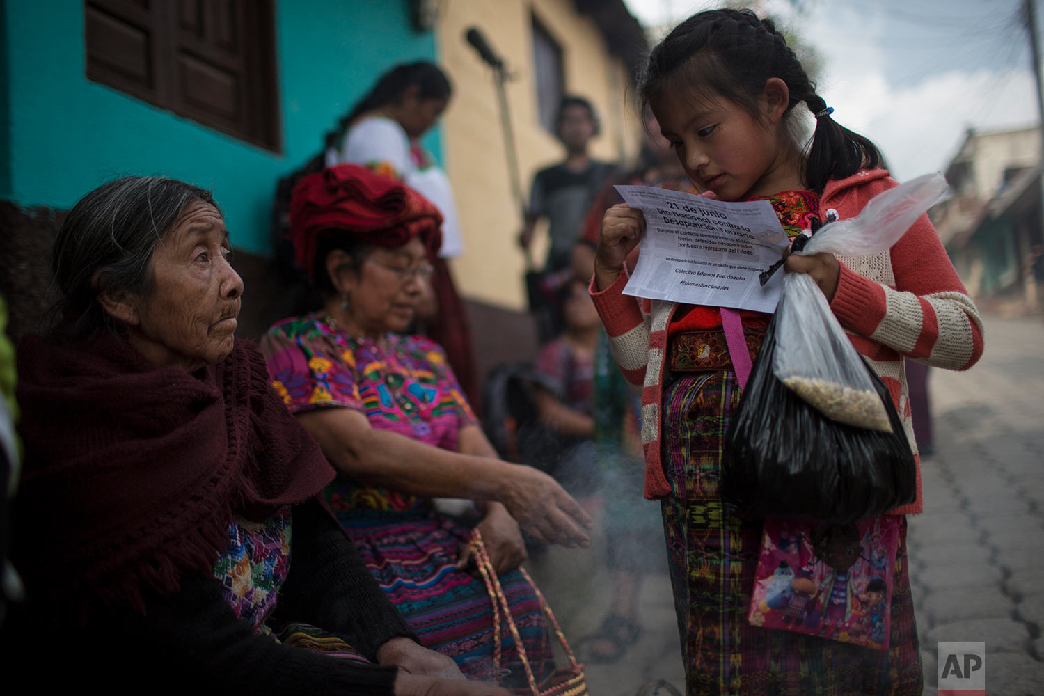 In this June 20, 2018 photo, a girl reads a paper announcing the National Day of Forced Disappearance during a funeral ceremony for 172 unidentified people who were dug up from a former military camp, one day before properly burying them in the same area they were discovered, in San Juan Comalapa, Guatemala. (AP Photo/Rodrigo Abd)