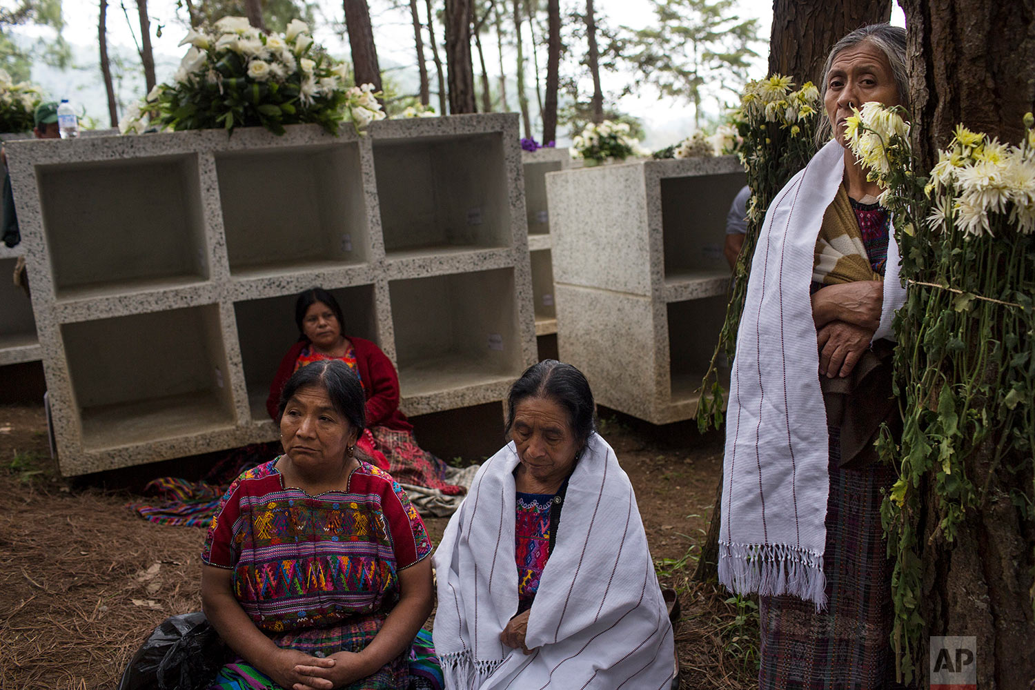 In this June 21, 2018 photo, women attend the funeral ceremony for 172 unidentified people who were discovered buried at what was once a military camp, during their proper burial ceremony at the same spot where they were found in San Juan Comalapa, Guatemala. (AP Photo/Rodrigo Abd)