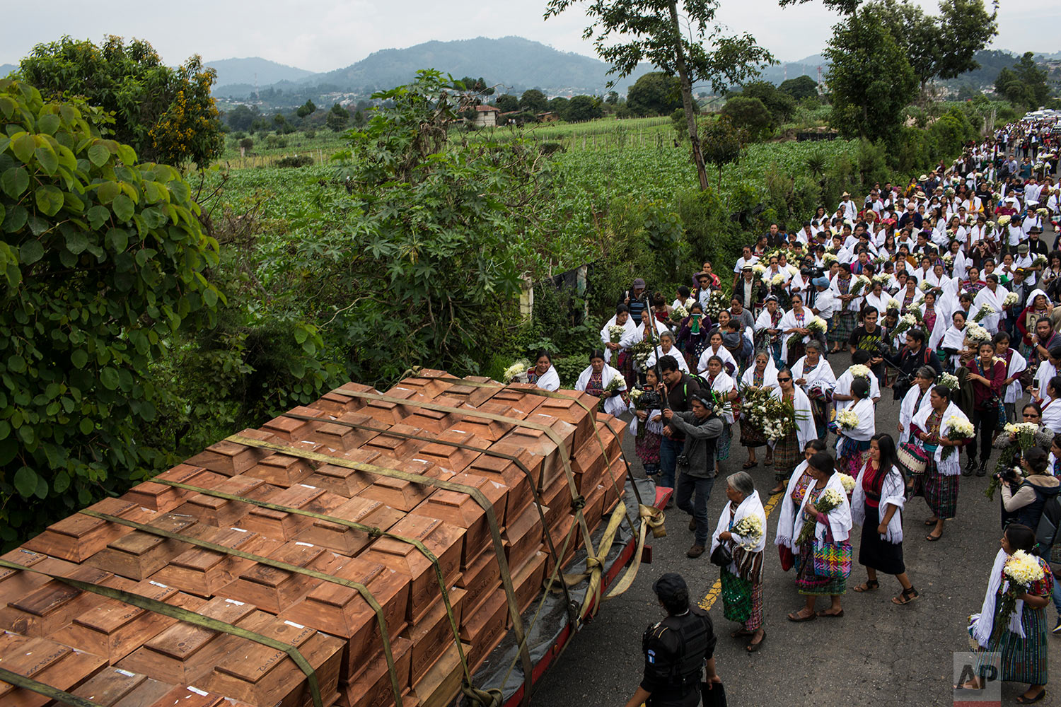 In this June 21, 2018 photo, villagers walk behind coffins during the funeral procession for 172 unidentified people who were exhumed from what was once a military camp, before burying them in the same area where they were discovered in San Juan Comalapa, Guatemala. (AP Photo/Rodrigo Abd)