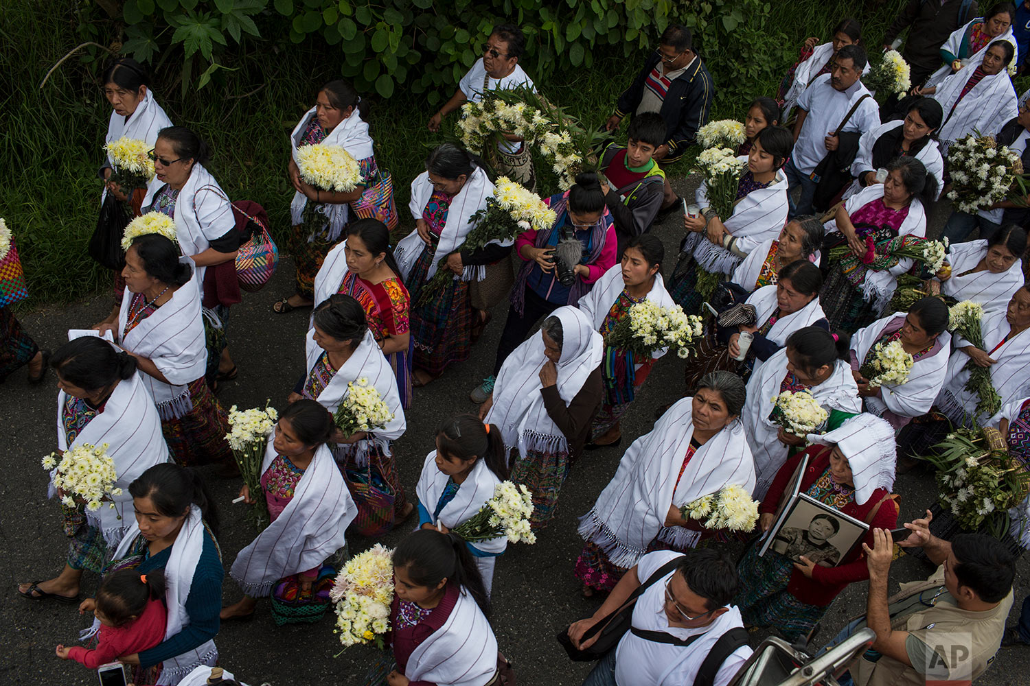 In this June 21, 2018 photo, women walk behind coffins during the funeral procession for 172 unidentified people who were found buried in a mass grave at what was once a military camp, to properly bury them in the same area where they were discovered in San Juan Comalapa, Guatemala. (AP Photo/Rodrigo Abd)