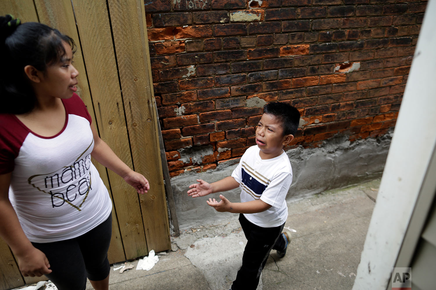 Carmelinda Perez tries to sooth her crying son, Franco, after he ran out of the house looking for his father in Florence, Ky. (AP Photo/Gregory Bull)