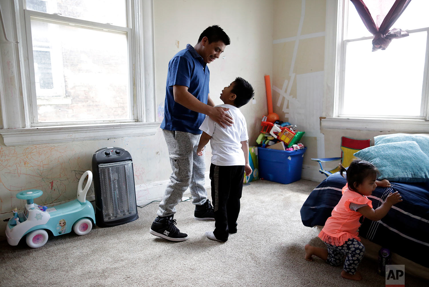 Edgar Perez Ramirez stands with his 4-year-old son, Franco, in their home. (AP Photo/Gregory Bull)