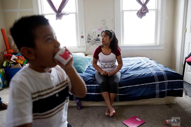 Franco Perez walks near his mother, Carmelinda, in their apartment in Covington, Ky. (AP Photo/Gregory Bull)