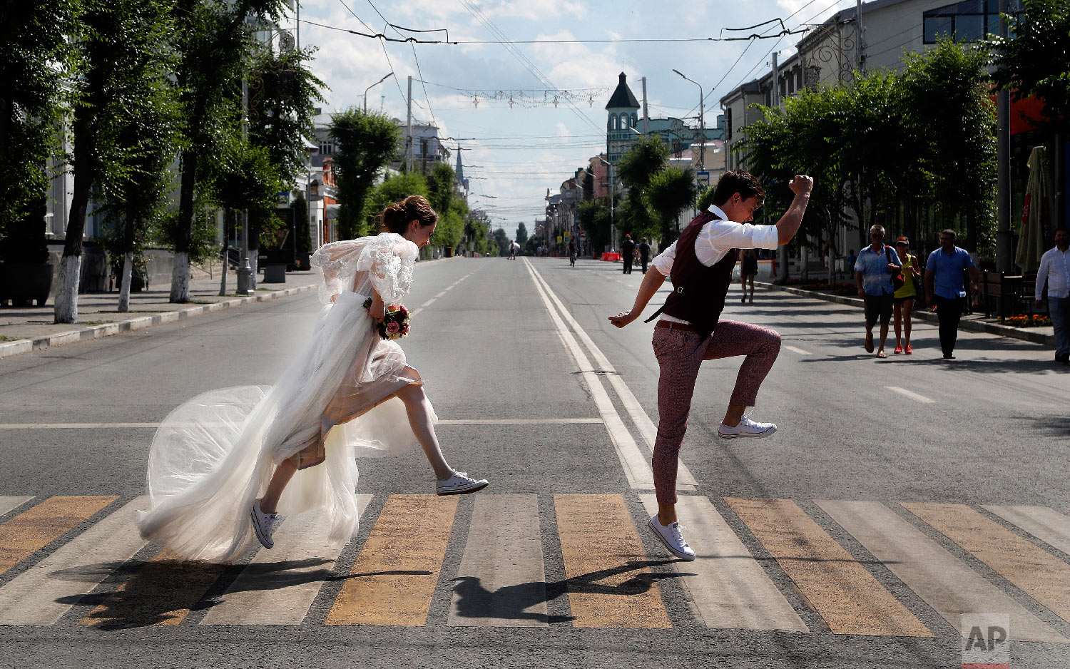 Newlyweds pose on a zebra crossing for wedding photographers during the 2018 soccer World Cup in Samara, Russia on Sunday, July 8, 2018. (AP Photo/Frank Augstein)