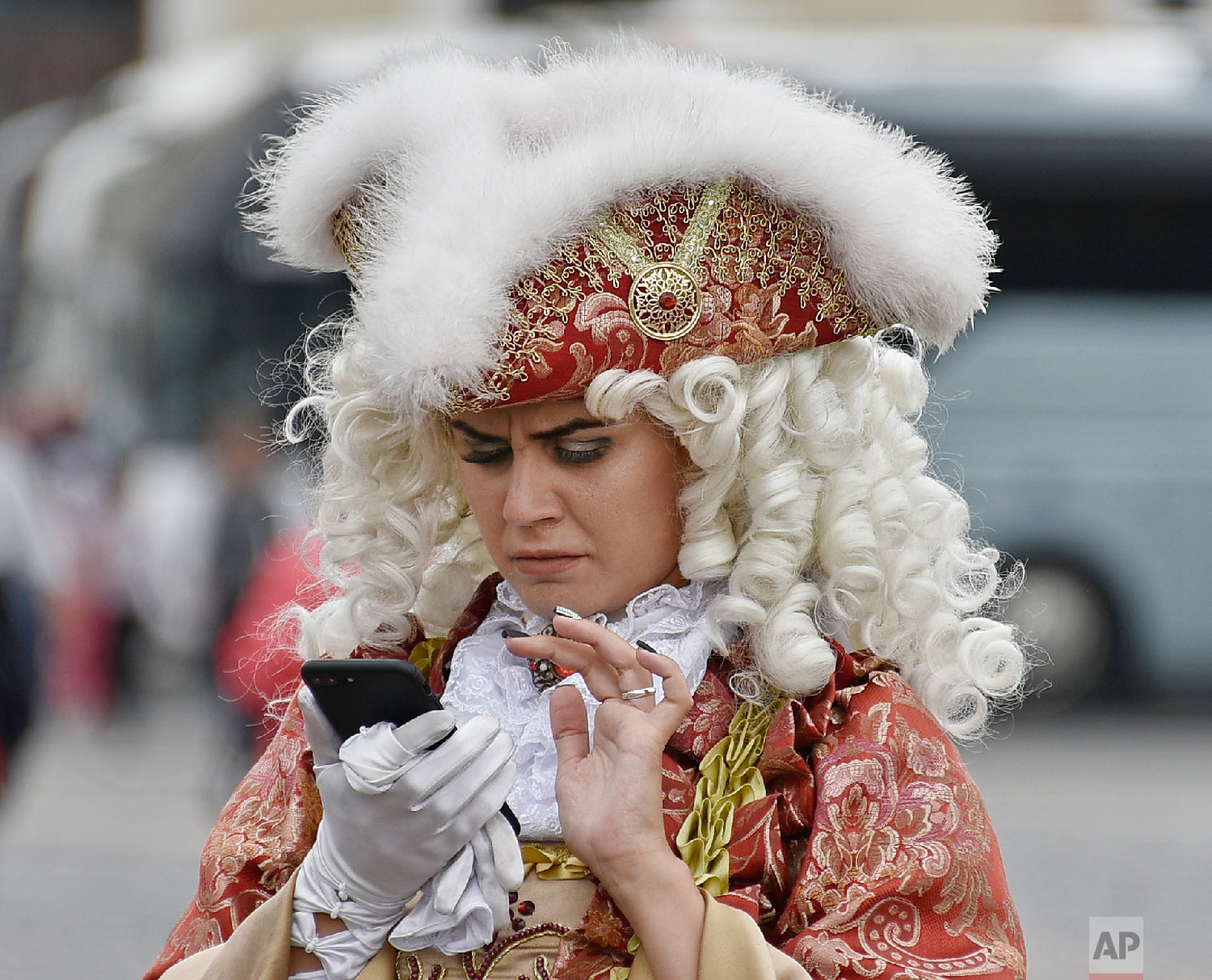 A woman dressed in a historic costume watches her smartphone in front of the Winter Palace during the 2018 soccer World Cup in St. Petersburg, Russia on Sunday, July 8, 2018. (AP Photo/Martin Meissner)
