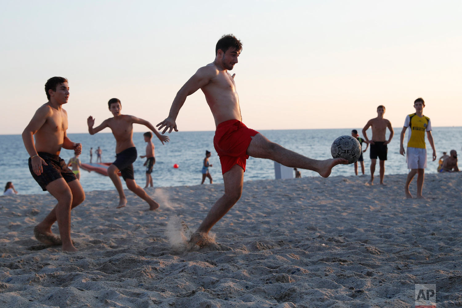 Men play soccer on the Black sea waterfront in Sochi, Russia during the 2018 soccer World Cup on Sunday, July 8, 2018. (AP Photo/Pavel Golovkin)