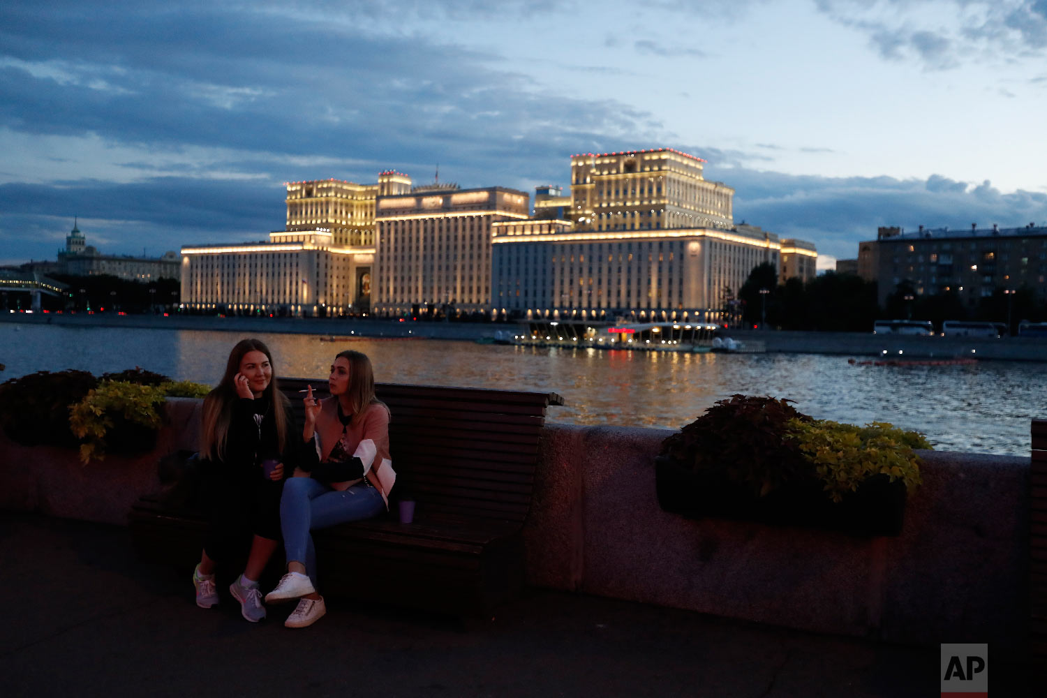 Women relax along the Moskva riverfront in Gorky Park as night falls, during the 2018 soccer World Cup in Moscow, Russia on Thursday, July 5, 2018. (AP Photo/Rebecca Blackwell)