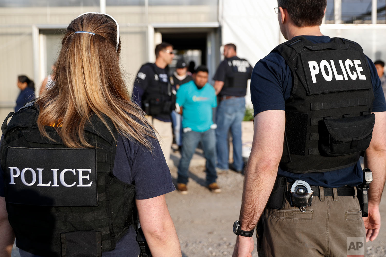 Government agents detain suspects during an immigration raid in Castalia, Ohio. (AP Photo/John Minchillo)
