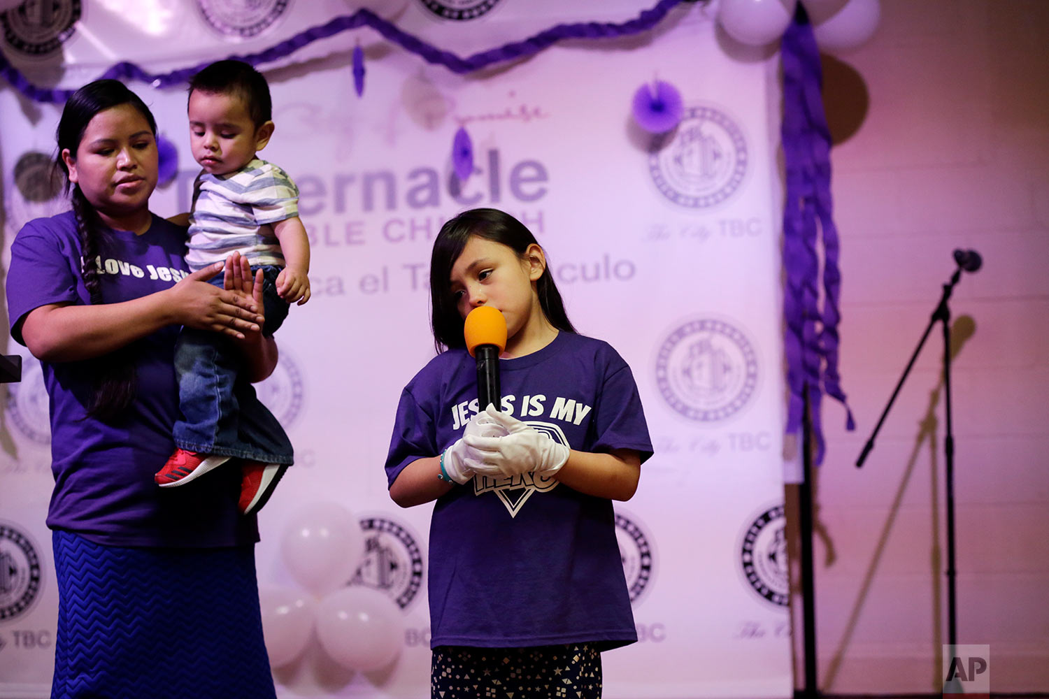 Holding her youngest son, Alma Vazquez stands next to her stepdaughter, Neveah Tomas, as she sings a song at a church event in Fairfield, Ohio, on April 28, 2018. A cousin who sometimes cares for the children told Vazquez that she recently heard them saying that if their father was deported, they'd have to leave the country, too. (AP Photo/Gregory Bull)
