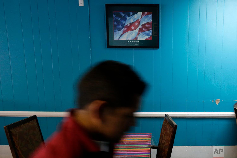 A man walks by a framed poster of a U.S. flag inside the Tercer Dia restaurant in Covington, Ky. (AP Photo/Gregory Bull)