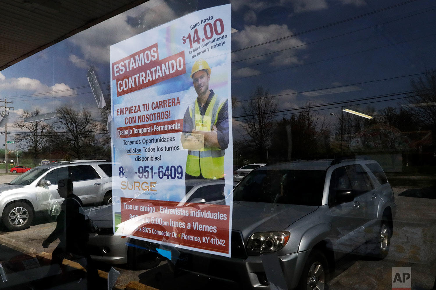 A poster announcing available jobs hangs in the window of the store La Guadalupana in Florence, Ky. (AP Photo/Gregory Bull)