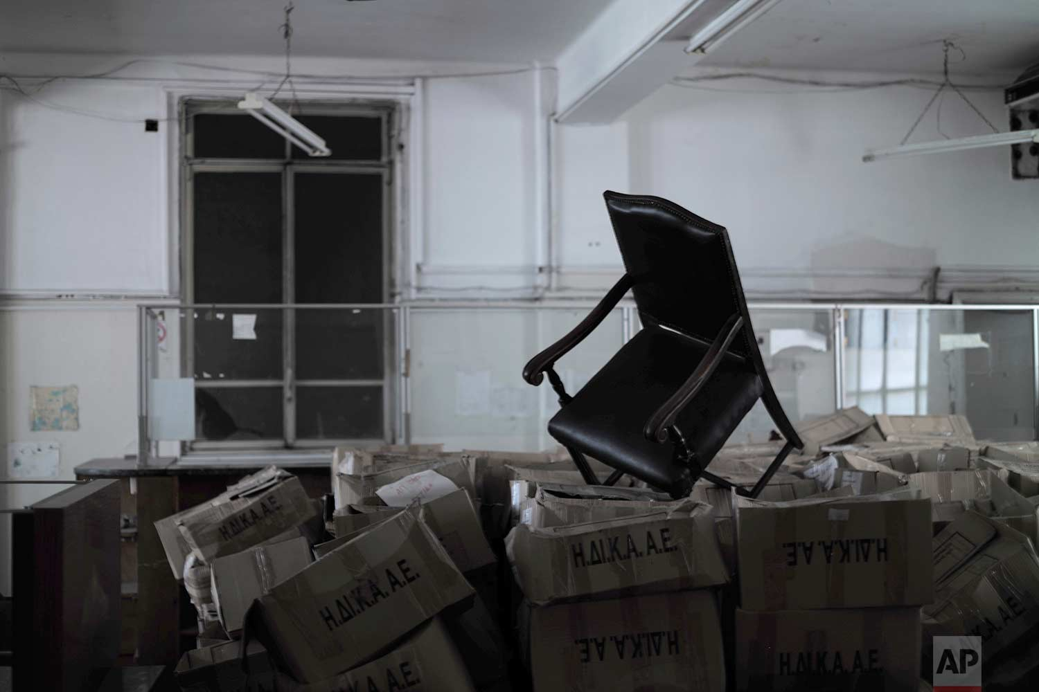 A chair is placed above boxes containing paper files in a 2,600-square meter listed building from 1955, formerly used by a commerce fund company. (AP Photo/Petros Giannakouris)