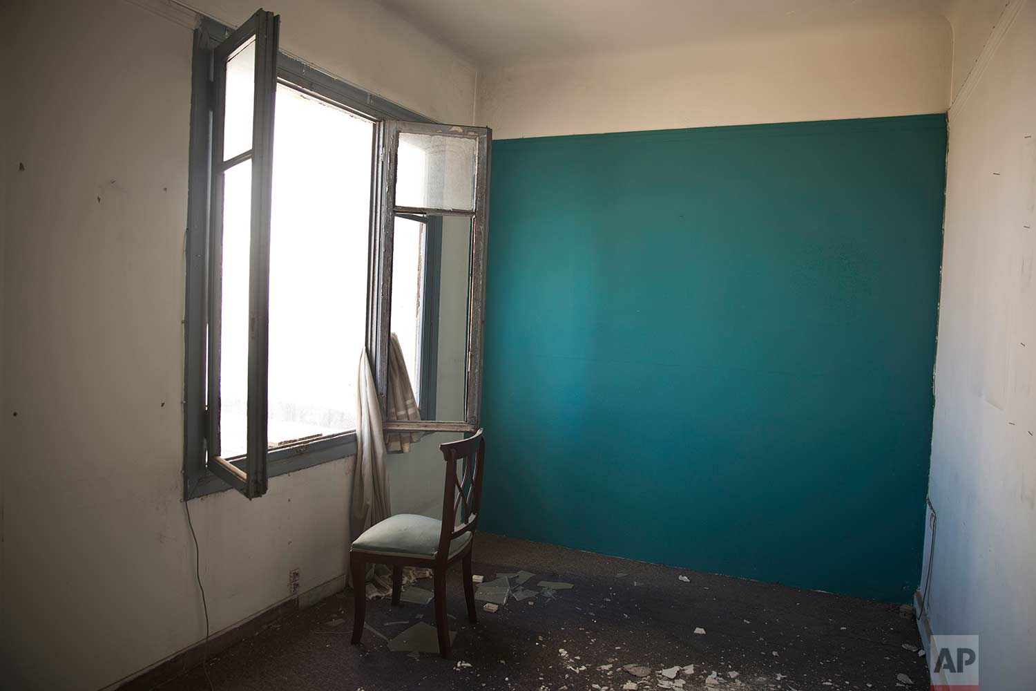 A chair in an empty room in one of Athens' few substantial late 19th century buildings to survive brutal postwar development. (AP Photo/Petros Giannakouris)