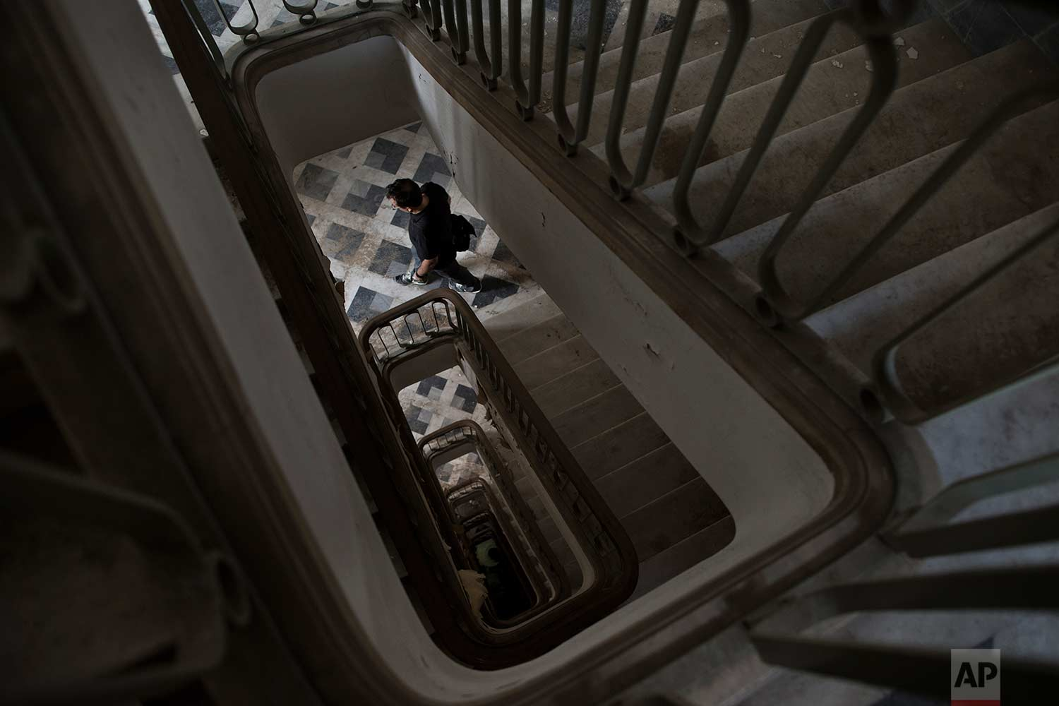 A pension fund employee walks down the marble stairs of a 2,600-square meter listed building from 1955, formerly used by a commerce fund company. (AP Photo/Petros Giannakouris)