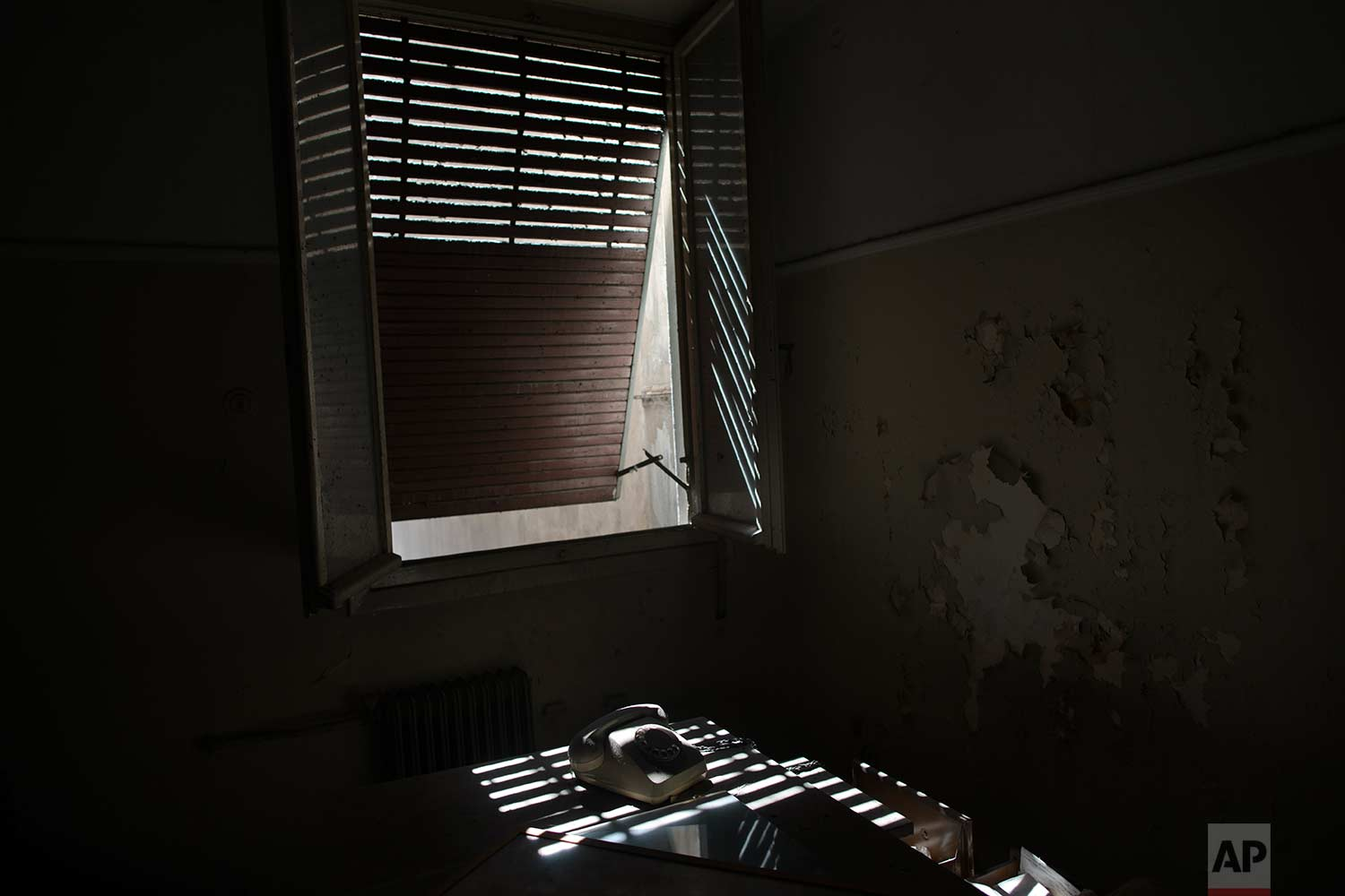 An old telephone is lit by bars of sunlight inside a 7-story block off central Athens' gritty Omonia Square, that has been untenanted since a now-defunct farm cooperative fund left years ago. (AP Photo/Petros Giannakouris)