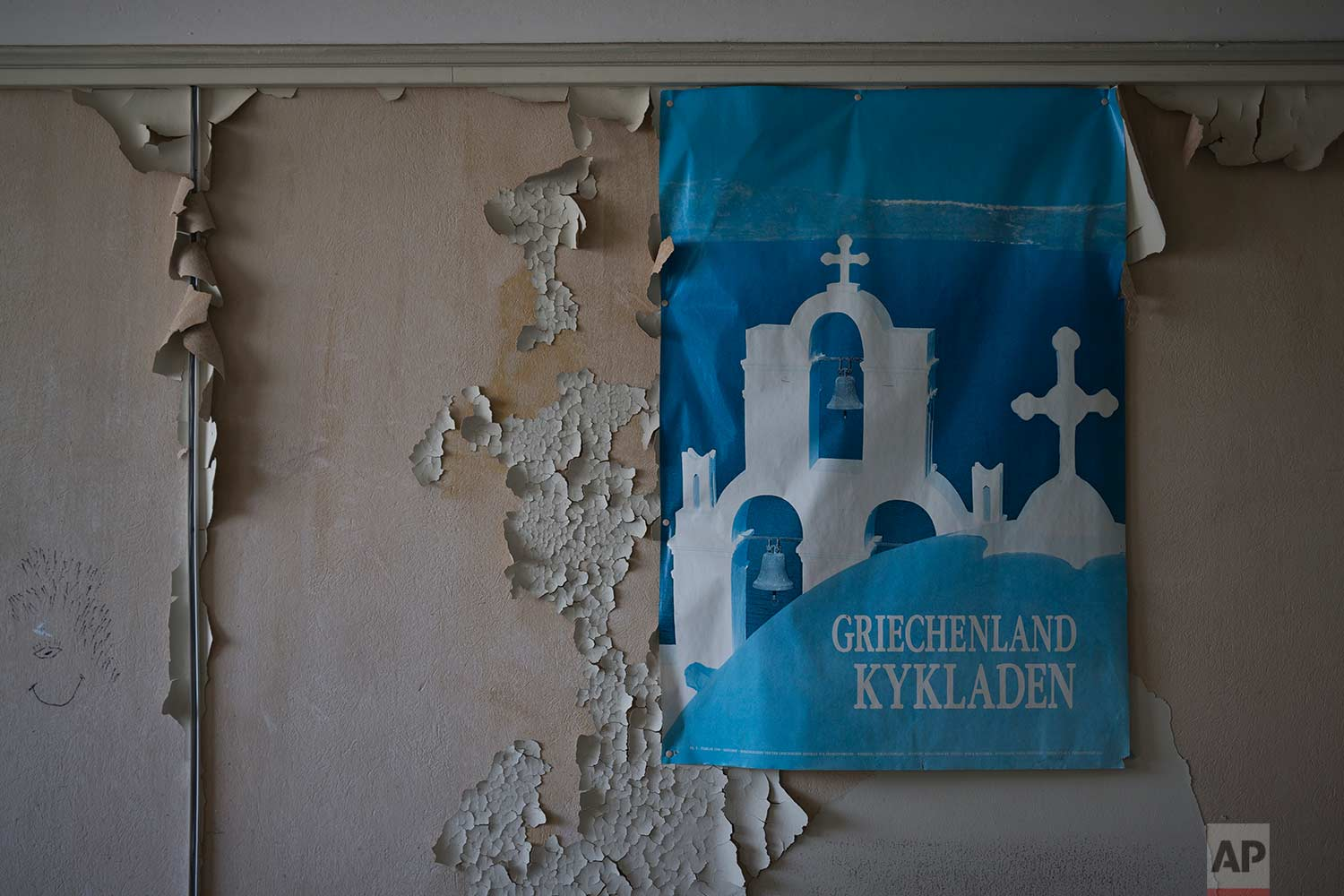 A Greek tourism board poster is displayed on a peeling wall in a 2,600-square meter listed building from 1955, formerly used by a commerce fund company. (AP Photo/Petros Giannakouris)