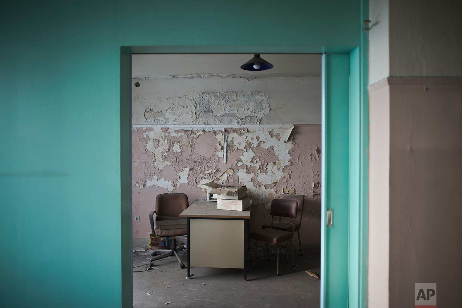 A metal desk and chairs by a peeling wall inside a 7-story block off central Athens' gritty Omonia Square, that has been untenanted since a now-defunct farm cooperative fund left years ago. (AP Photo/Petros Giannakouris)