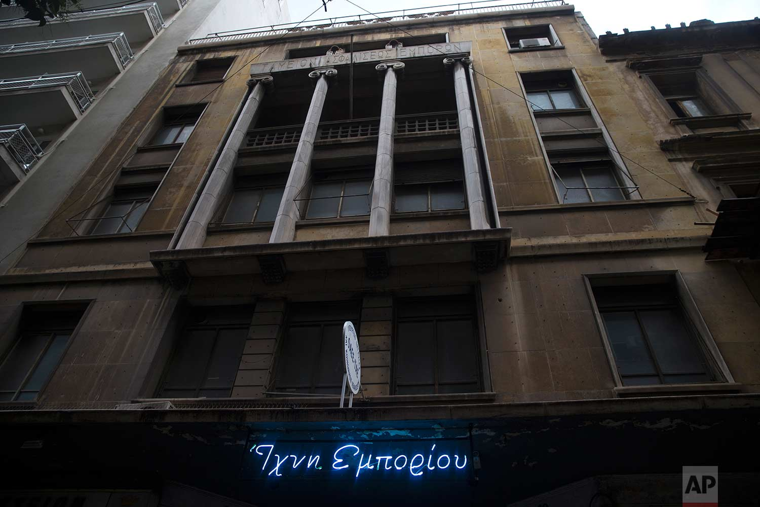 """The facade of a 2,600-square meter listed building from 1955, formerly used by a commerce fund company. The sign, from an old art installation, reads """"Traces of commerce."""" (AP Photo/Petros Giannakouris)"""
