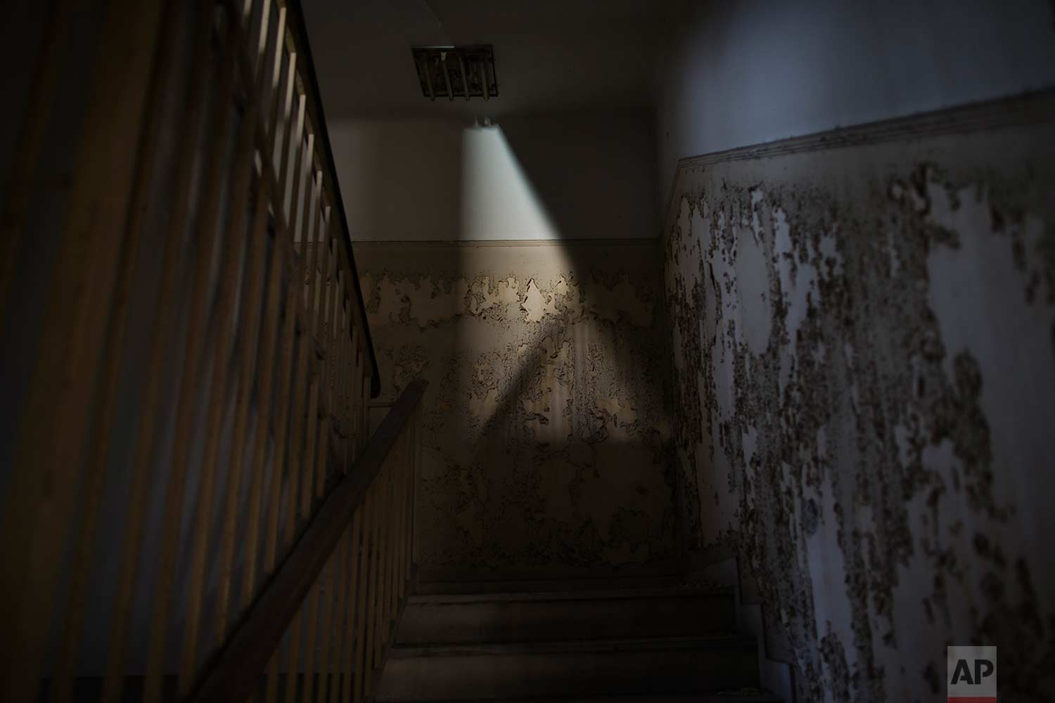 Peeling walls by a staircase inside a 7-story block off central Athens' gritty Omonia Square, that has been untenanted since a now-defunct farm cooperative fund left years ago. (AP Photo/Petros Giannakouris)