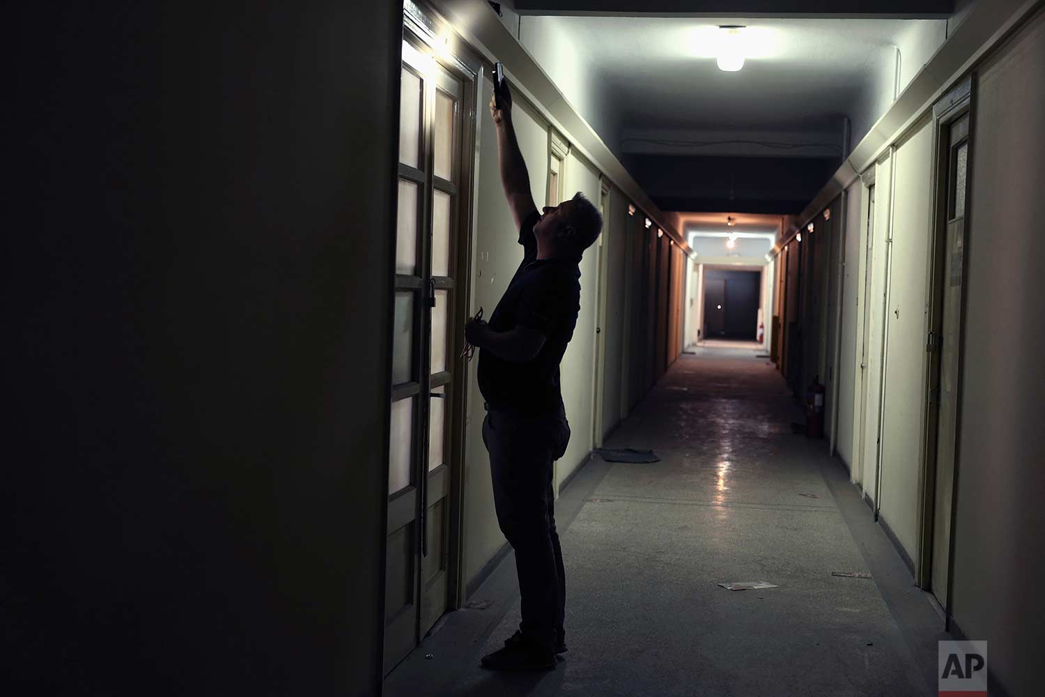 A pension fund employee in an office doorway in one of Athens' few substantial late 19th century buildings to survive brutal postwar development. (AP Photo/Petros Giannakouris)