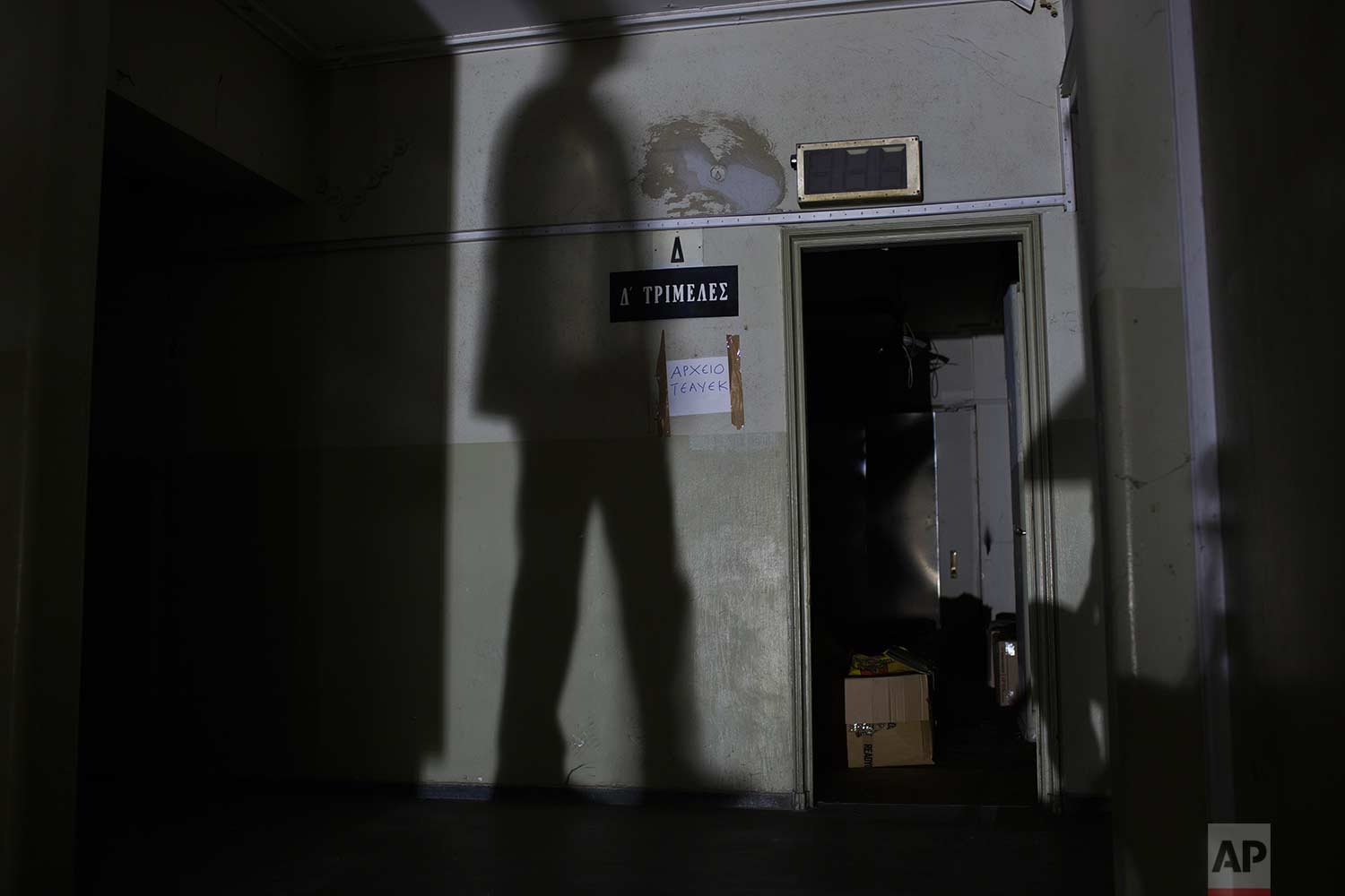 """A man's shadow appears next to a sign reading """"Three-member Court"""" in the former Ambassadeur hotel in Athens. (AP Photo/Petros Giannakouris)"""