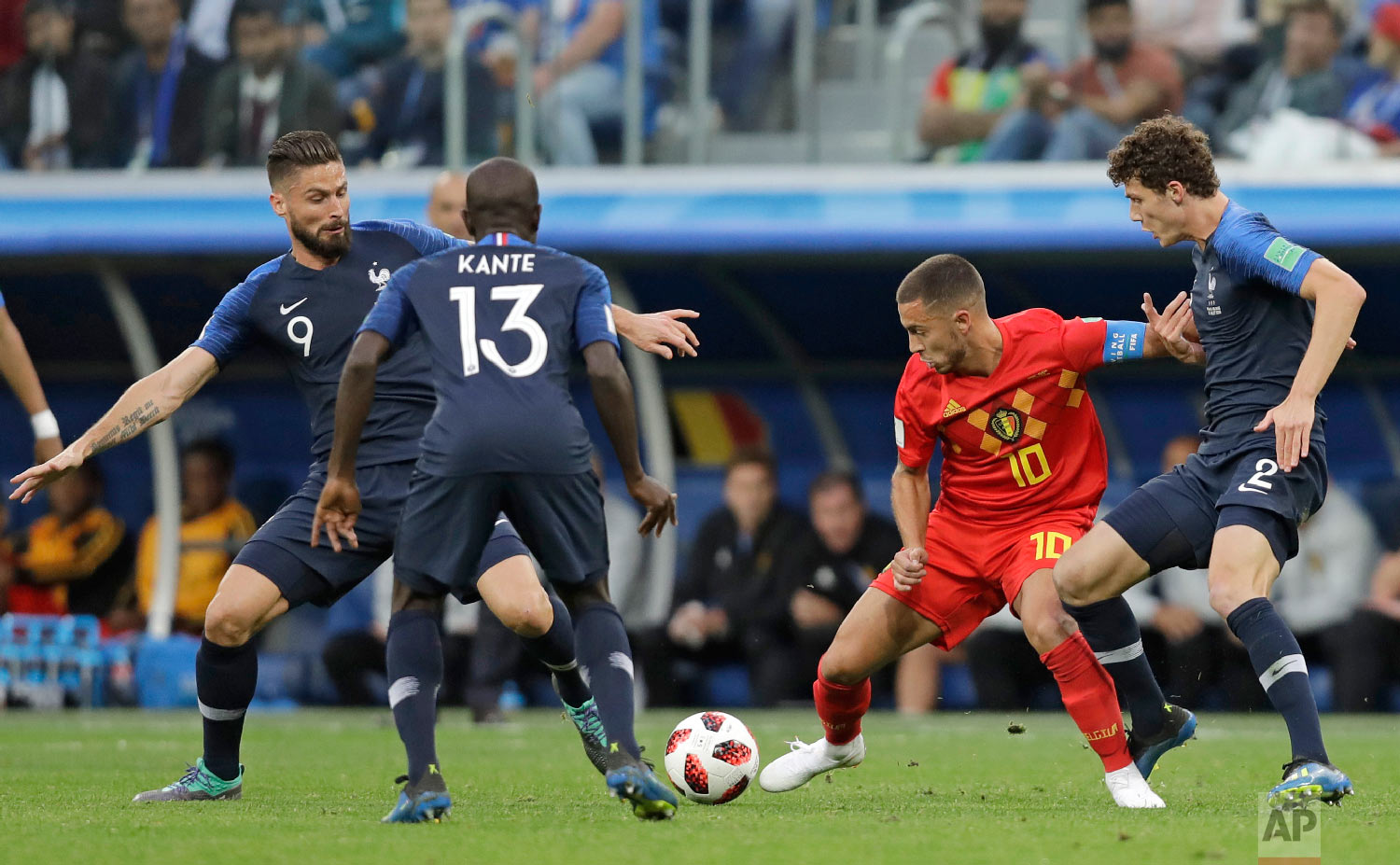 Belgium's Eden Hazard, second right is challenged for the ball by France's Benjamin Pavard, right and France's Olivier Giroud left, during the semifinal match between France and Belgium at the 2018 soccer World Cup in the St. Petersburg Stadium in, St. Petersburg, Russia, Tuesday, July 10, 2018. (AP Photo/Natacha Pisarenko)