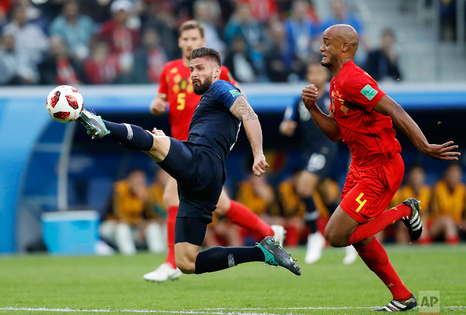 France's Olivier Giroud, left, tries to control the ball with Belgium's Vincent Kompany during the semifinal match between France and Belgium at the 2018 soccer World Cup in the St. Petersburg Stadium, in St. Petersburg, Russia, Tuesday, July 10, 2018. (AP Photo/David Vincent)
