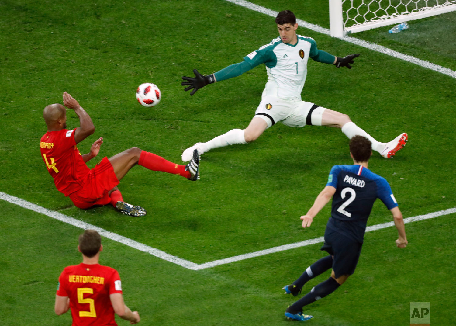 Belgium goalkeeper Thibaut Courtois, top right, makes a save in front of France's Benjamin Pavard, right, during the semifinal match between France and Belgium at the 2018 soccer World Cup in the St. Petersburg Stadium in St. Petersburg, Russia, Tuesday, July 10, 2018. (AP Photo/Pavel Golovkin)