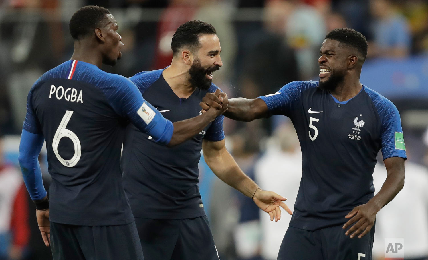 France's Samuel Umtiti, right celebrates with teammates France's Adil Rami, centre and France's Paul Pogba after defeating Belgium in their semifinal match between France and Belgium at the 2018 soccer World Cup in the St. Petersburg Stadium in, St. Petersburg, Russia, Tuesday, July 10, 2018. France won the game 1-0. (AP Photo/Natacha Pisarenko)