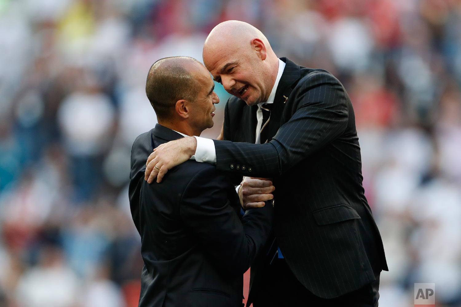 FIFA President Gianni Infantino, right, talks to Belgium coach Roberto Martinez after the third place match between England and Belgium at the 2018 soccer World Cup in the St. Petersburg Stadium in St. Petersburg, Russia, Saturday, July 14, 2018. (AP Photo/Natacha Pisarenko)
