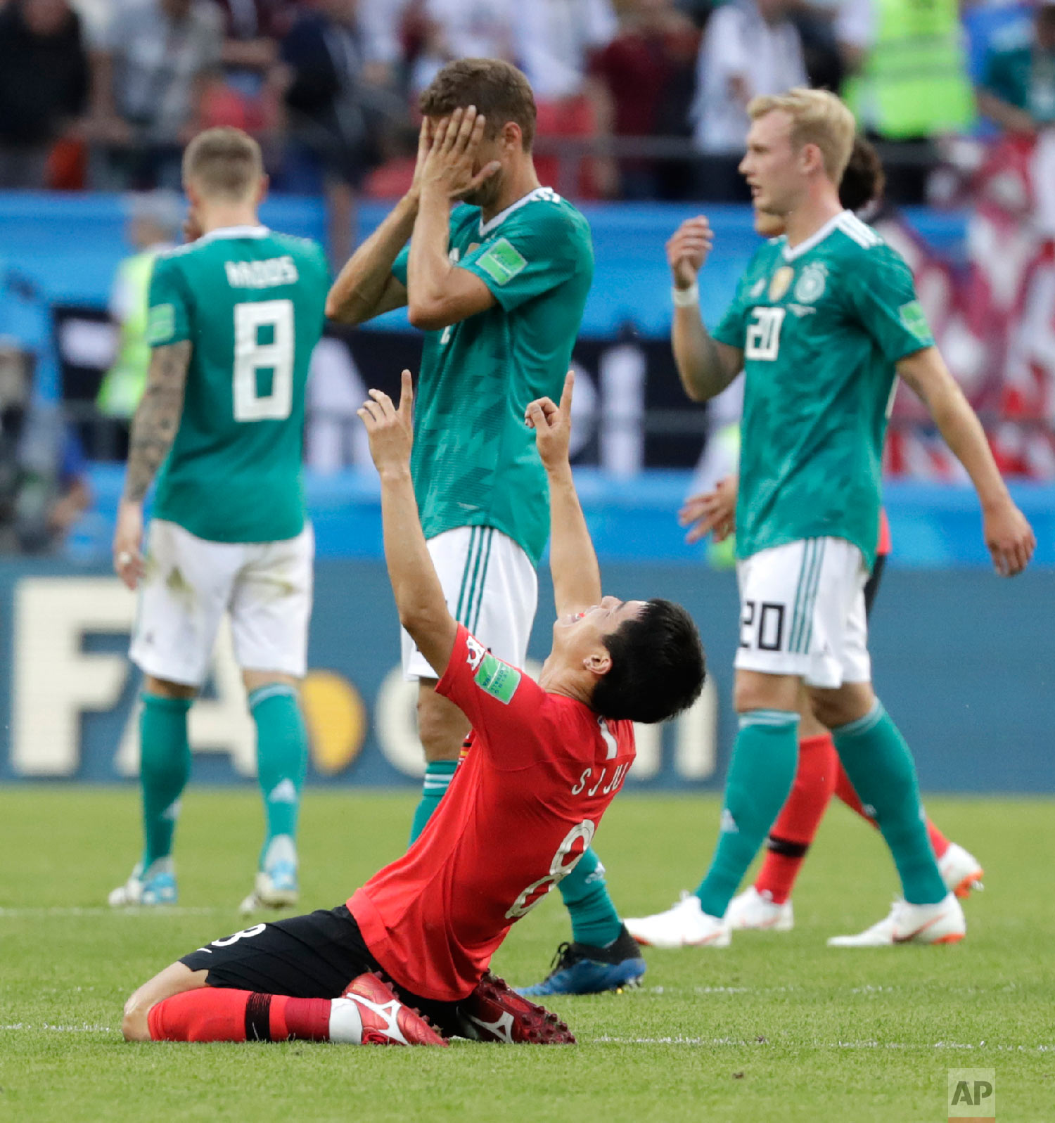 Germany's players walk off the pitch as South Korea's Ju Se-jong, front celebrates after the group F match between South Korea and Germany, at the 2018 soccer World Cup in the Kazan Arena in Kazan, Russia on June 27, 2018. (AP Photo/Lee Jin-man)