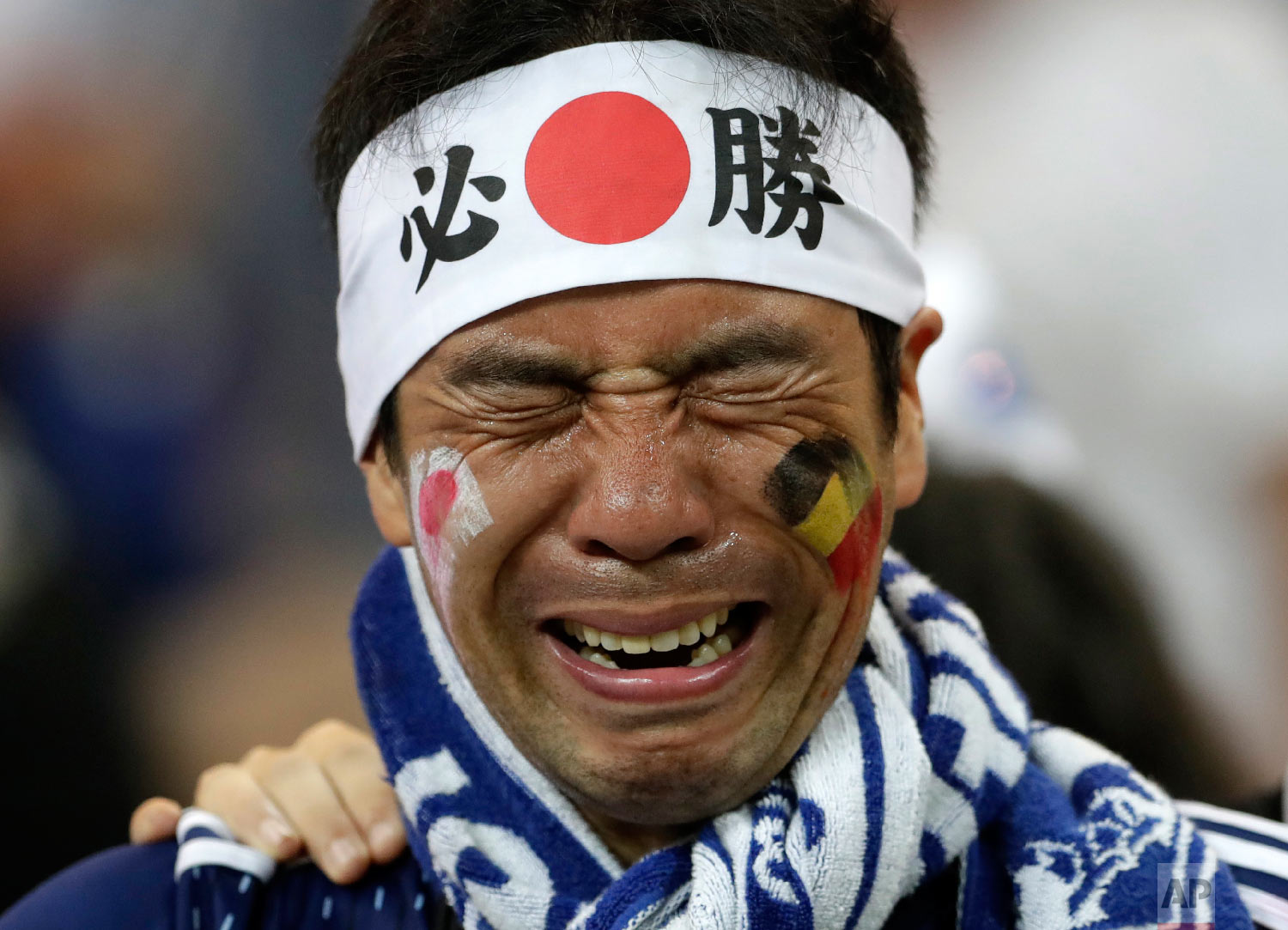 A Japan supporter cries after losing the round of 16 match between Belgium and Japan at the 2018 soccer World Cup in the Rostov Arena, in Rostov-on-Don, Russia, Monday, July 2, 2018. (AP Photo/Petr David Josek)