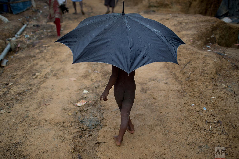 In this Monday, June 25, 2018, file photo, a Rohingya child refugee carries an umbrella as he walks through Kutupalong refugee camp in Bangladesh. (AP Photo/Wong Maye-E)